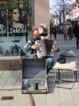 Street musician and dog jointly playing the accordian