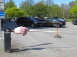 One parking lot is guarded by a hand holding a baton